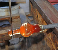By using long metal tools he is able to pinch to glass and pull on it forming the stem of the glass.