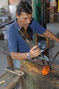 The artisan is sculpting end of the hot ball of glass to make the desired glass piece.